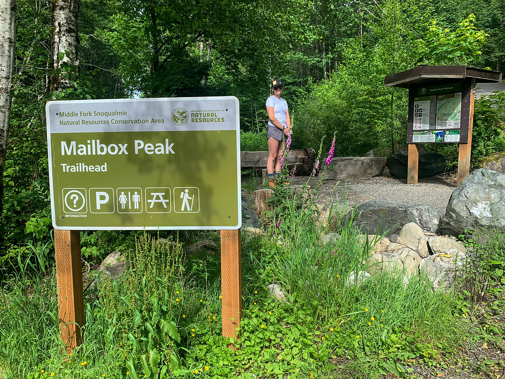 Girl standing next to mailbox peak trailhead sign