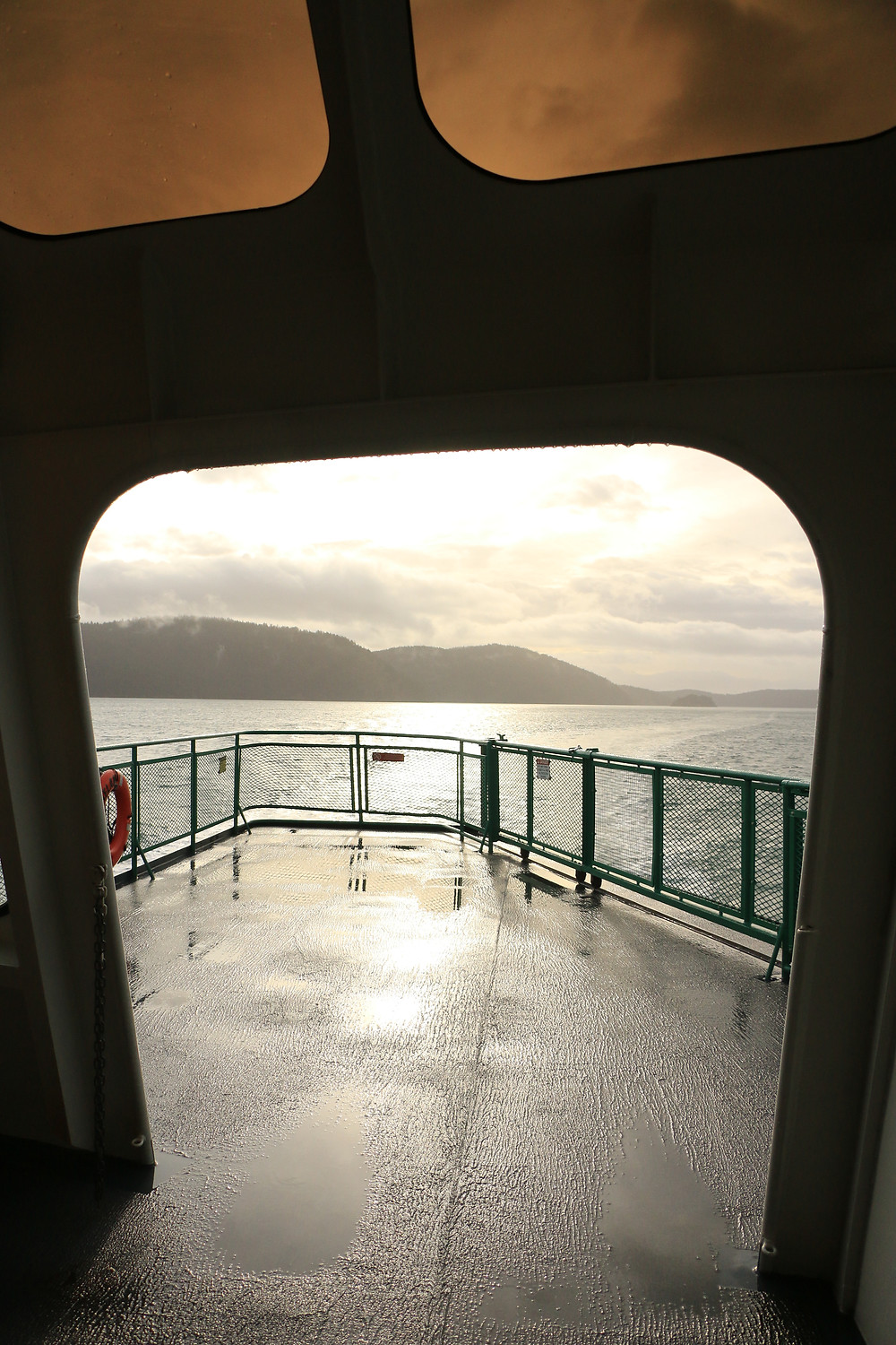 picture of mountains through doorway of a ferry