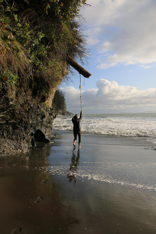 girl grabbing rope swing on mystic beach