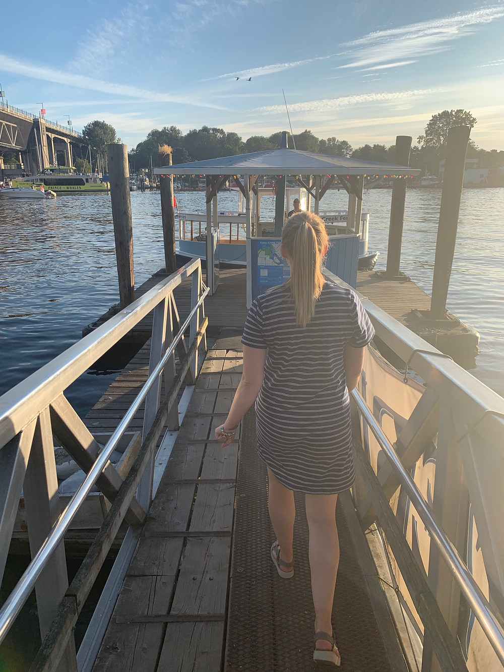 Girl walking down dock to false creek ferry in Vancouver