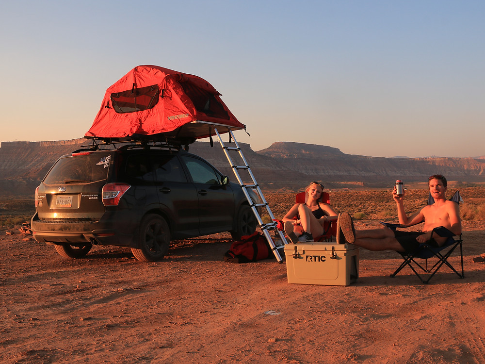 two people sitting in a campsite with a rooftop tent