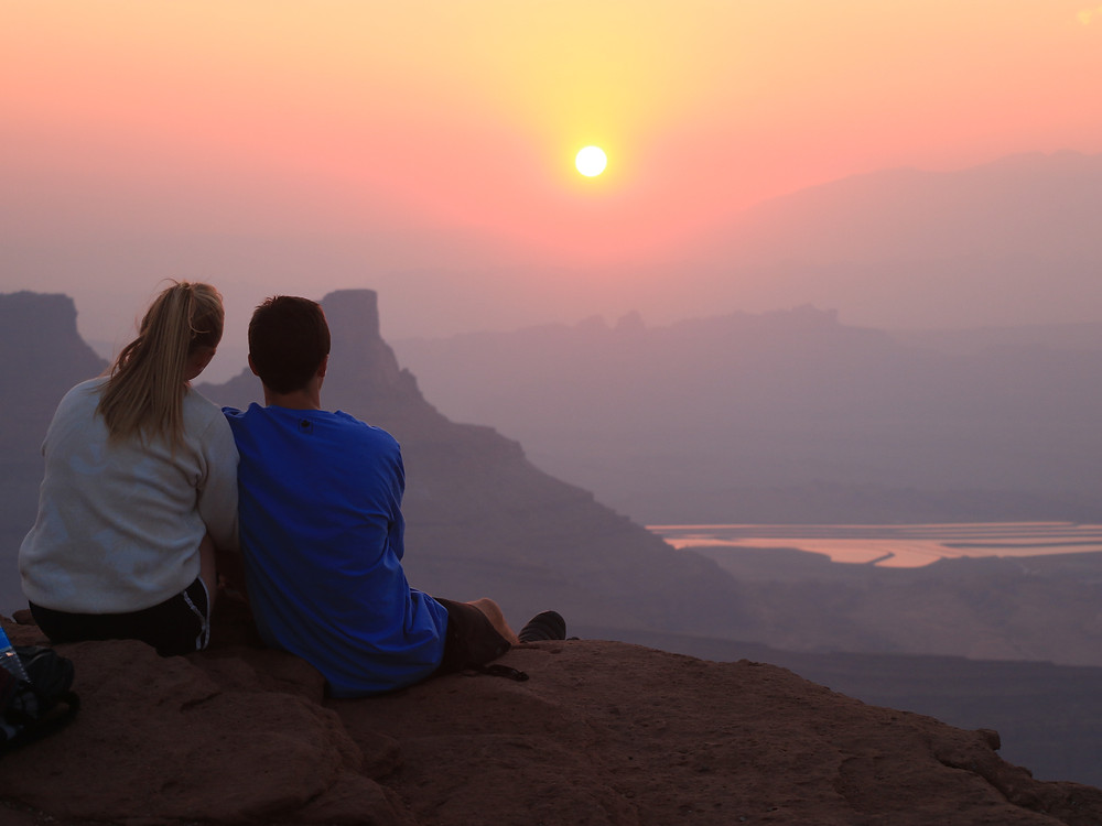Two people watching the sun rise over Moab