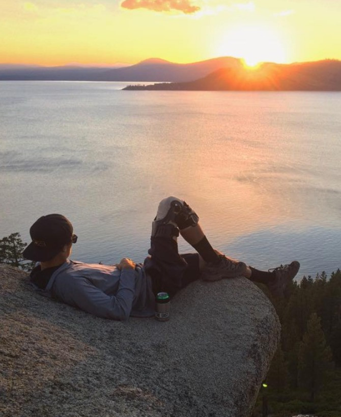 Man sitting on a rock watching sunset over lake tahoe