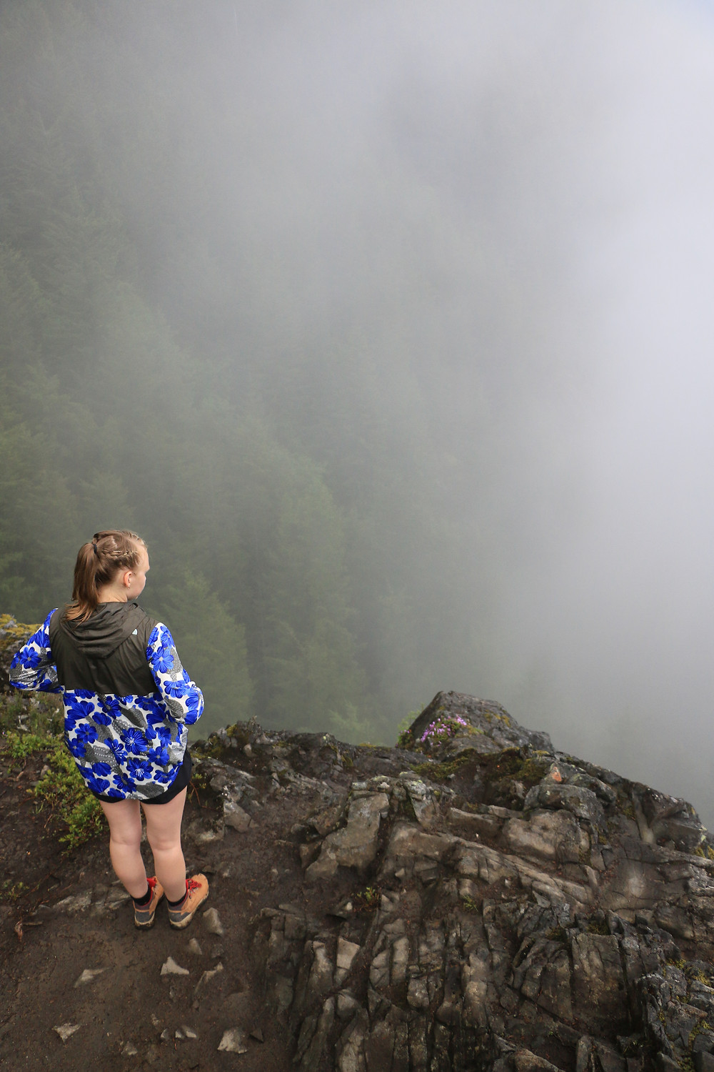 Girl standing on cliff of Dirty Harry's Balcony looking in to the fog