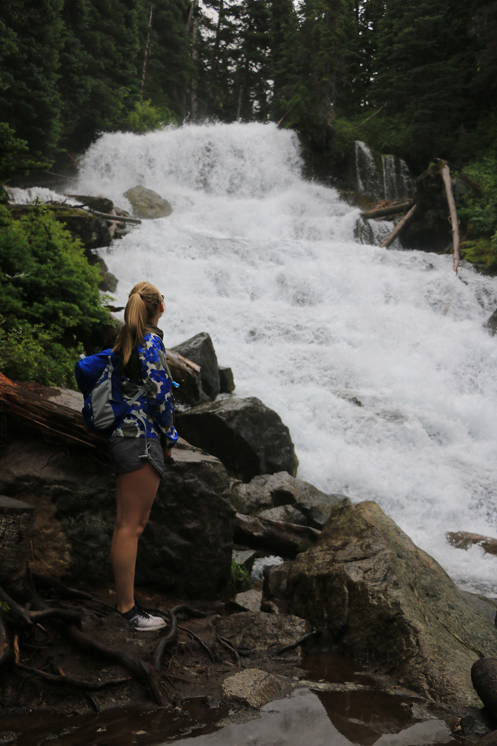 Girl staring at waterfall in Joffre Lakes Provincial Park