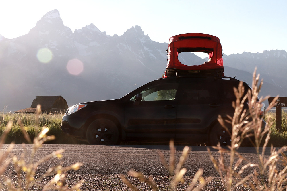 A car with a rooftop tent parked in front of the Grand Teton
