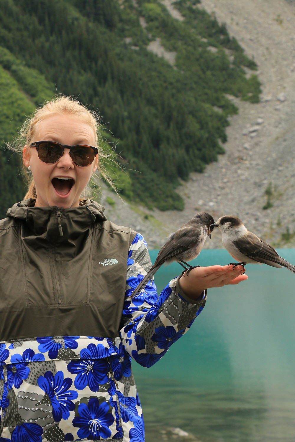 Girl holding two birds on her hand at Upper Joffre Lake