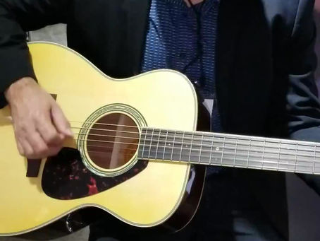 Our guitar teacher Phil Ernst at NAMM, checking out a Yamaha LS6 acoustic guitar.