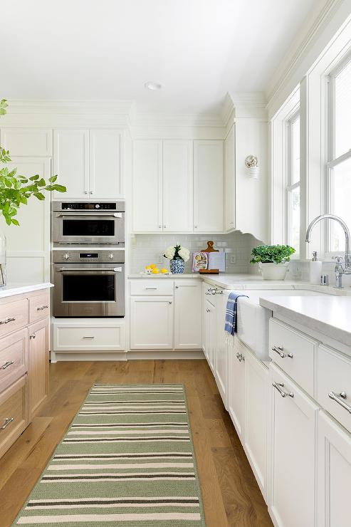 A striped rag rug creates a feel of illusion for narrow kitchens