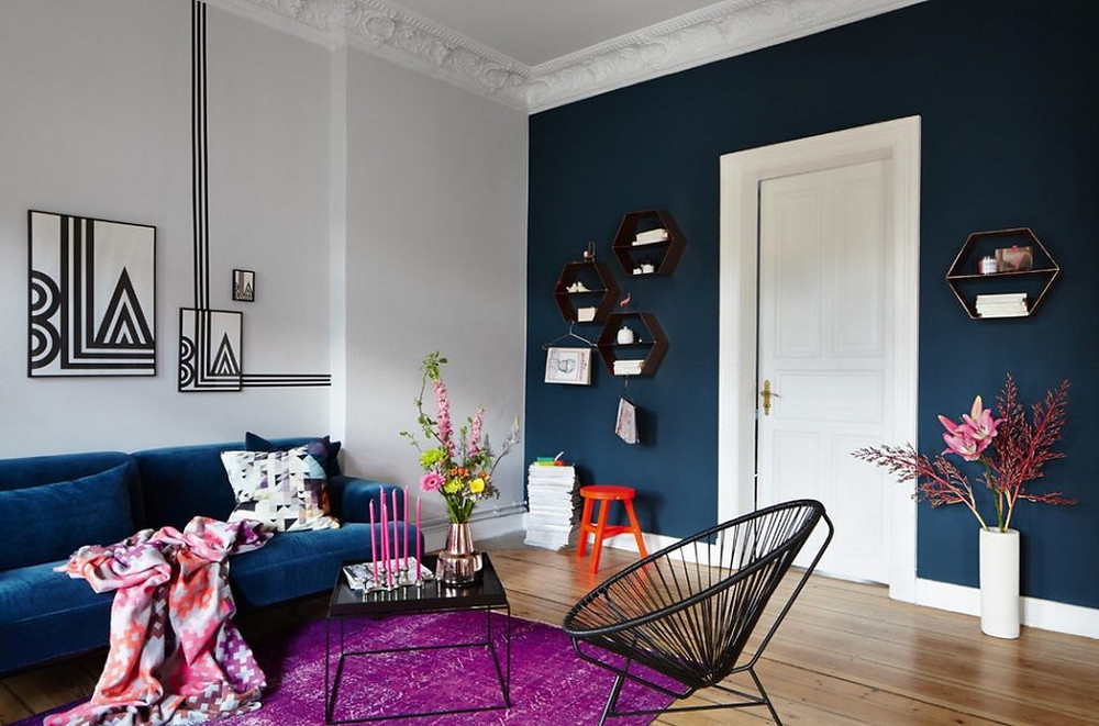 The blue-green color on one of the walls of the living room gives a classy look