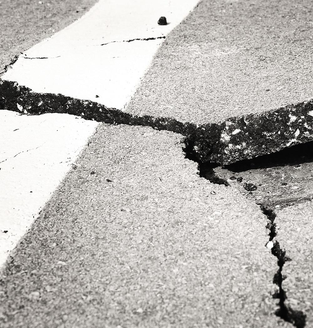 a large crack in a piece of asphalt.