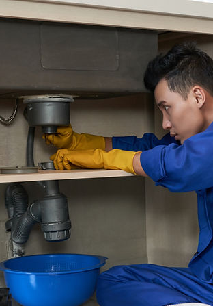 asian-plumber-blue-overalls-clearing-blo