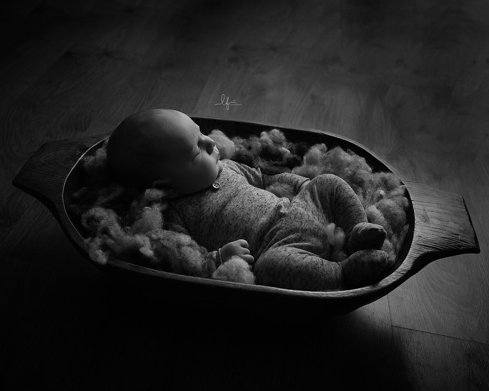 black and white photo of baby boy in bowl asleep