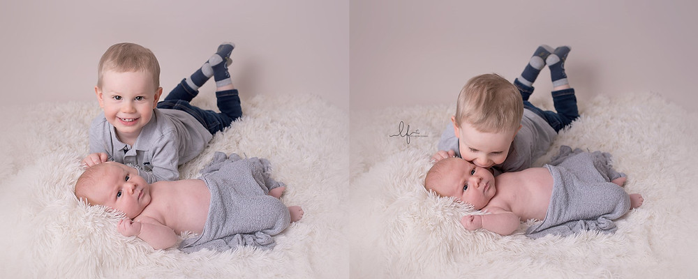 big brother laying down with his new little brother, giving him a kiss