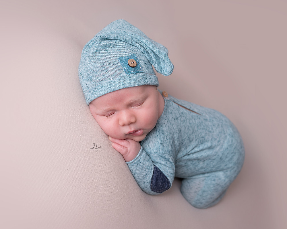 sleepy 4 week old baby boy in green romper and hat