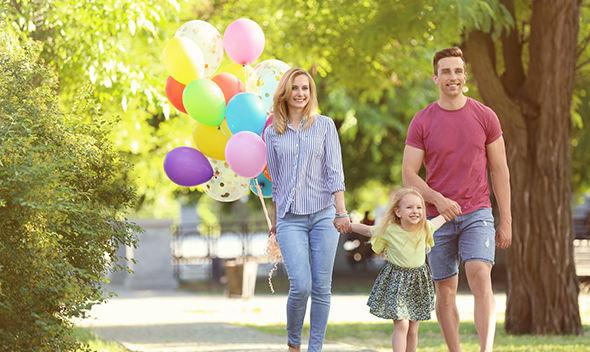 Fröhliche Familie mit Luftballons beim Spazieren