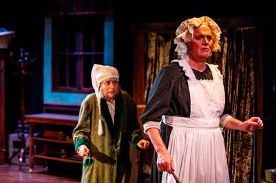 Carine Montbertrand as Ebenezer Scrooge and Wynn Harmon as Mrs. Dilber  A Christmas Carol Titan Theatre Company