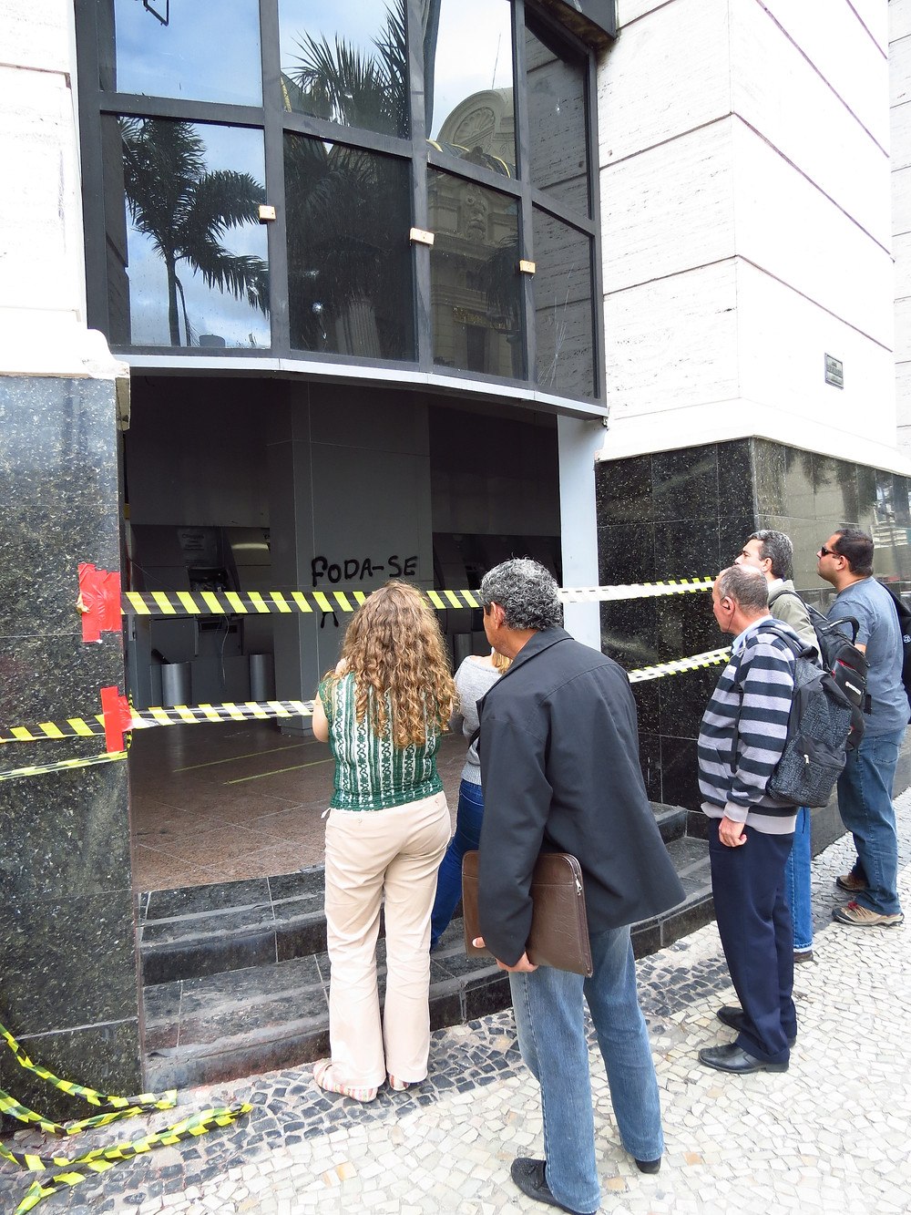 5. Bank of Brazil, Cinelandia square, Rio de Janeiro, 7 November 2013. The bank was hit and vandalized by protesters the night before. Passers-by are looking at the traces left by the range just a few hours earlier, with the darkness of the night.