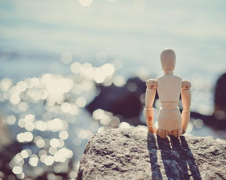 Bildet viser en liten trefigur sem ser utover havet i flott solskinn. Bildet illustrerer noe vi mennesker assosierer med å være glad og velvære. Bli kvitt hodepine, verkende rygg, sykefravær, mm i en effektiv og smertefri behandling av dine nakke og ryggsmerter.