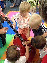 Kids strumming guitar