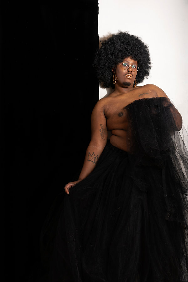 The second photo from the photography series. The subject is now facing and looking into the camera, holding part of the tulle skirt.