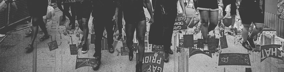 """Image Description: A black and white digital collage. The images feature members of Black Lives Matter Toronto marching at Pride Toronto in 2017 juxtaposed over an image of the Pride March on University Avenue in Toronto in 1972. The images were photographed by Mark Blinch and Jerald Moldenhauer, respectively. Over the images is a button that says """"memory & time"""" that, when clicked, will take you to the """"About"""" page."""