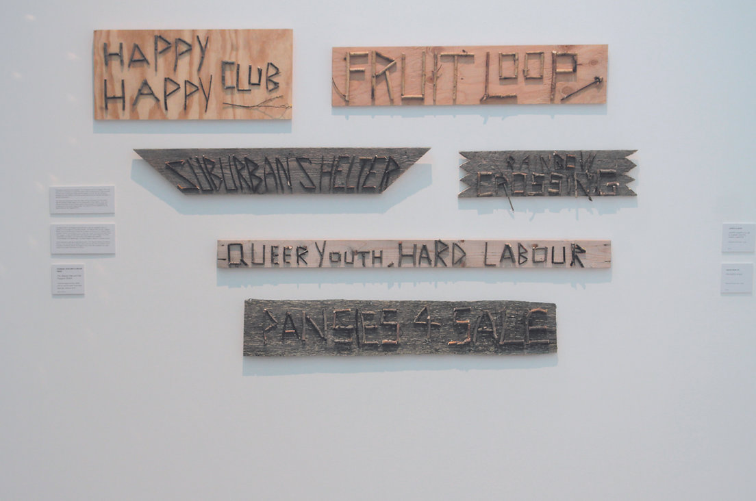 Results from The Beaver Mat & The Fag(g)ot Shack workshop from 2014 by Hannah & Helen. The image features a series of wooden panels with phrases.