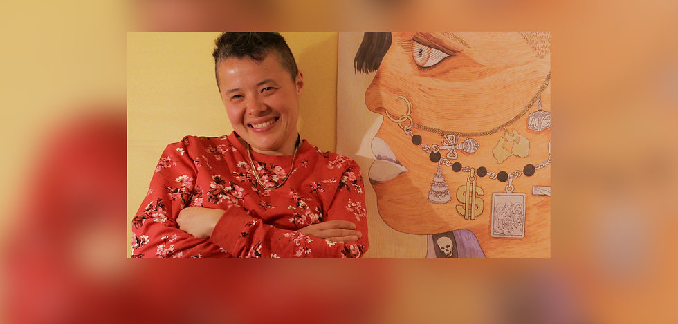 """A colour picture of Elisha Lim. They are wearing a red sweatshirt with a cherry-blossom pattern and a chain. They have a cropped haircut and is smiling into the camera. They stand beside the artwork """"Subcultural Charm"""" by Textaqueen."""