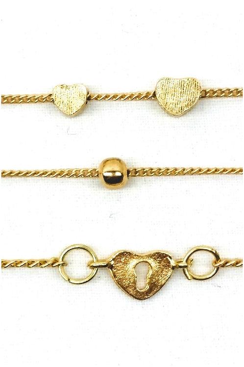 Lot de trois bracelets charm's chaînette dorée cœur, perle et serrure