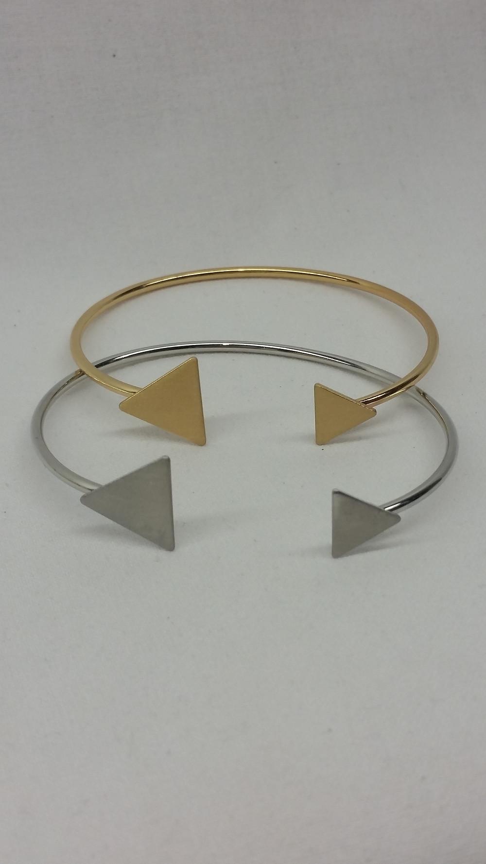 BRACELET JONC CHARM TRIANGLE Joli bracelet jonc charm en métal doré avec triangles pleins en métal doré à chaque extrémité, de tailles différentes. Graphique et minimaliste, il habille votre poignet de façon discrète et élégante