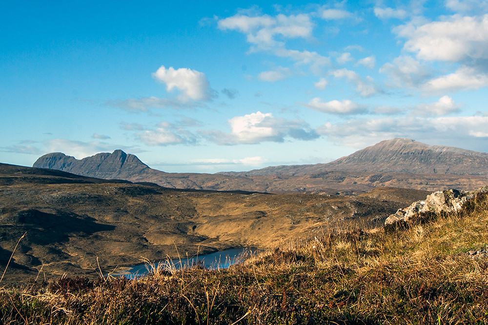 A wide vista looking across moorland to the mountains of Suilven and Canisp