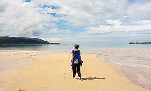 Single lady walking barefoot towards the sea on Balnakiel beach, on the NC500.