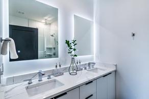 Vanities and backlit mirrors in master bathroom ensuite