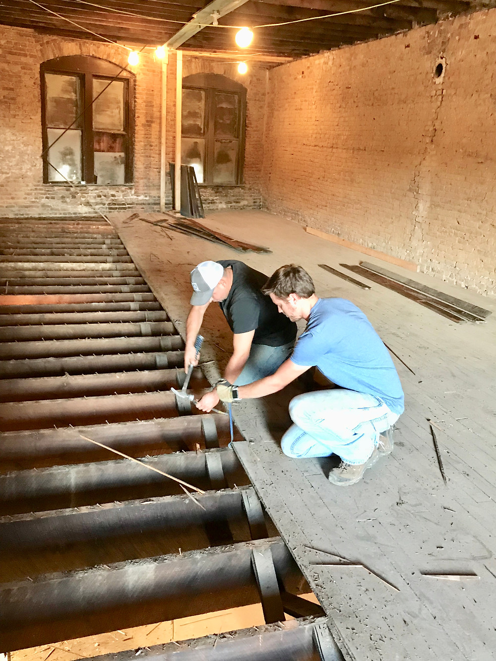 Sam Martin and Josue Rivas try to preserve the floors at the House of Vaccums, East Florence, AL Sweetwater District