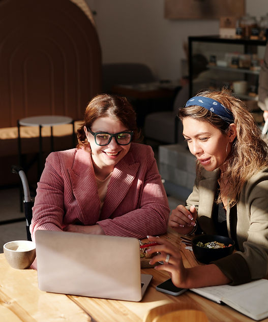 Two women sat at a table working on a laptop