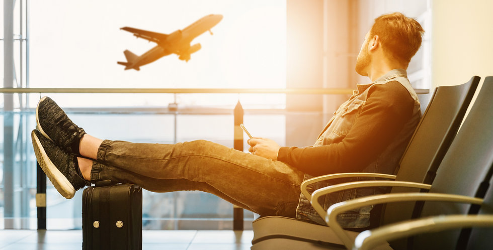 man sitting on gang chair with feet on luggage looking at airplane_edited.jpg