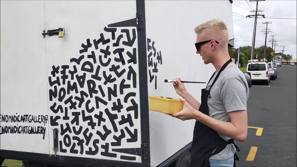 Artist Oliver Cain live painting on the outside of the Nomadic Art Gallery
