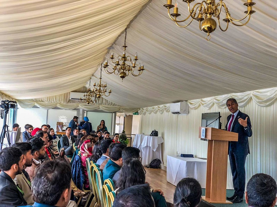 Alpesh Patel speaking in Parliament to an audiance from India speaking about finance, inclusion and education