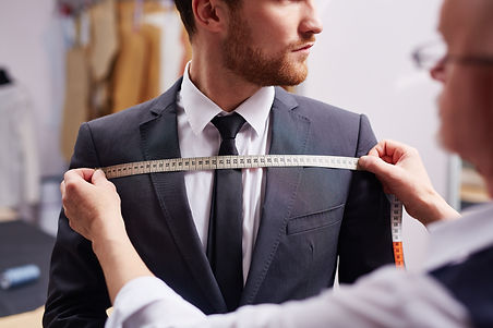Mid section portrait of tailor fitting b