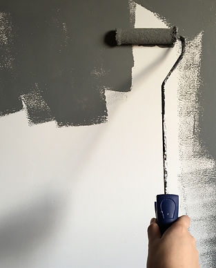 person-holding-paint-roller-while-painti