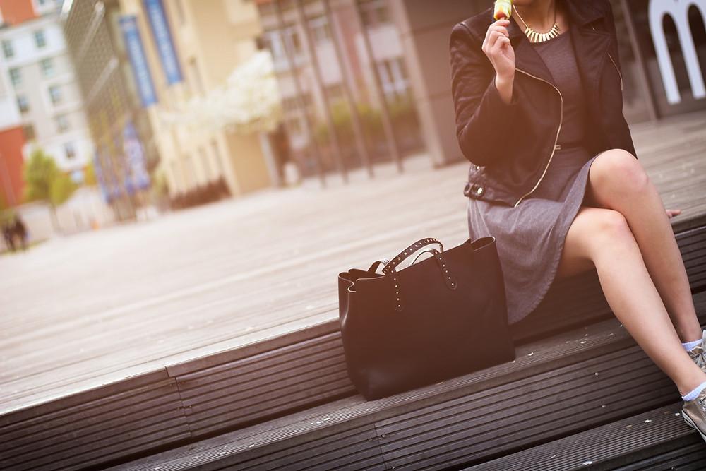 Beautiful woman sitting on steps with handbag