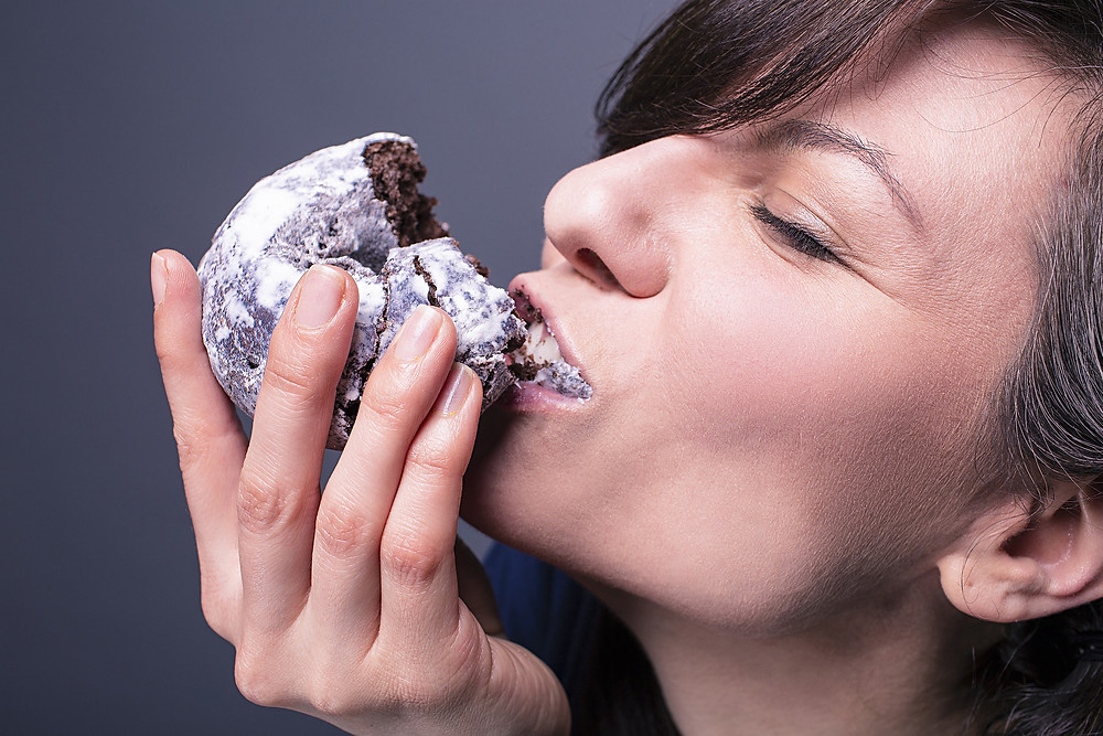 Woman stuffing face with donut