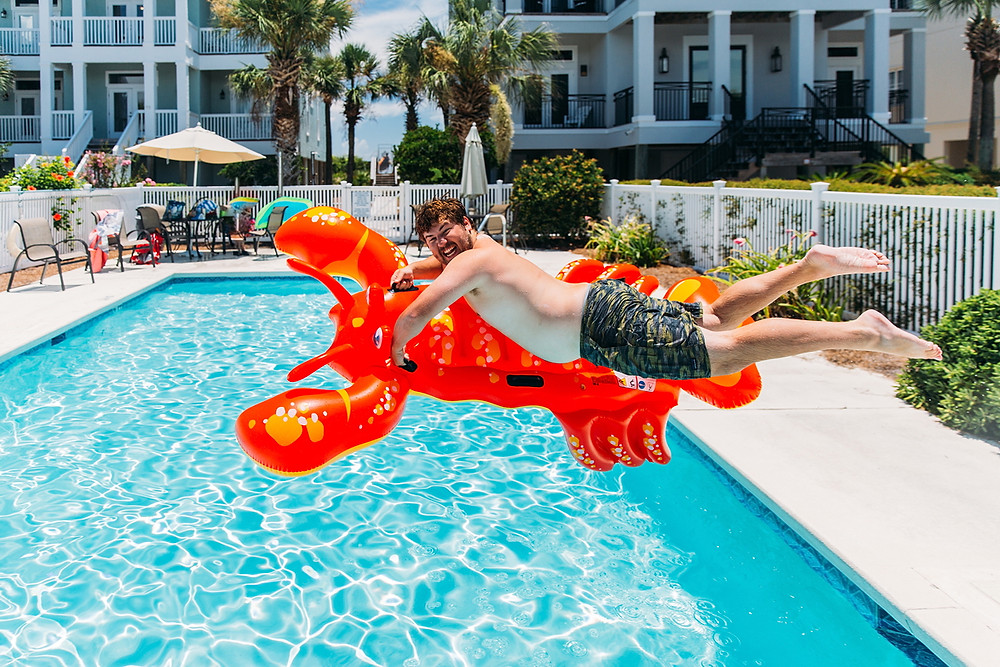 Man leaping into pool on a lobster floating toy