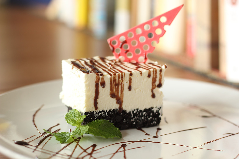 Slice of cheesecake with chocolate syrup drizzled on top