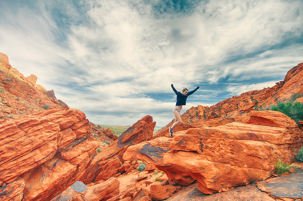 Woman running on red rock mountain top