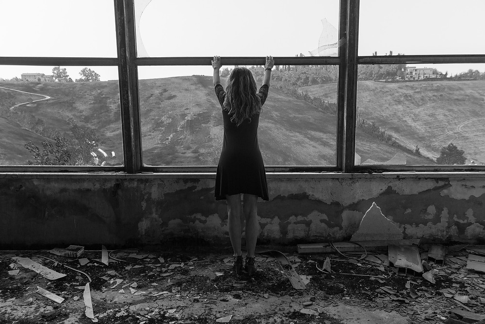Desolate woman in abandoned building looking out window