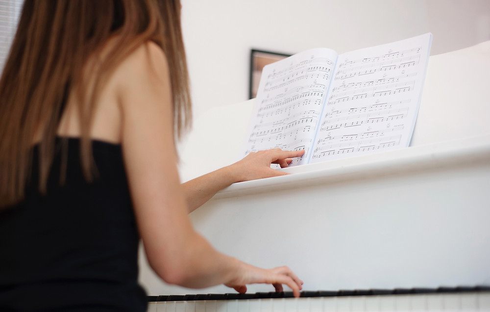 a girl practicing piano notes and sightreading