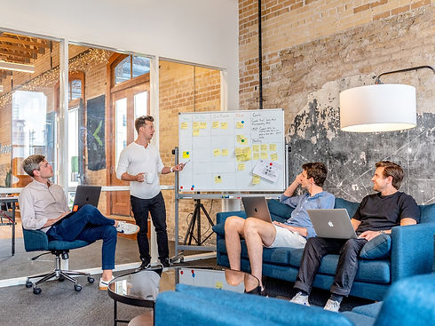 4 men in a meeting looking at a whiteboard covered in post it notes