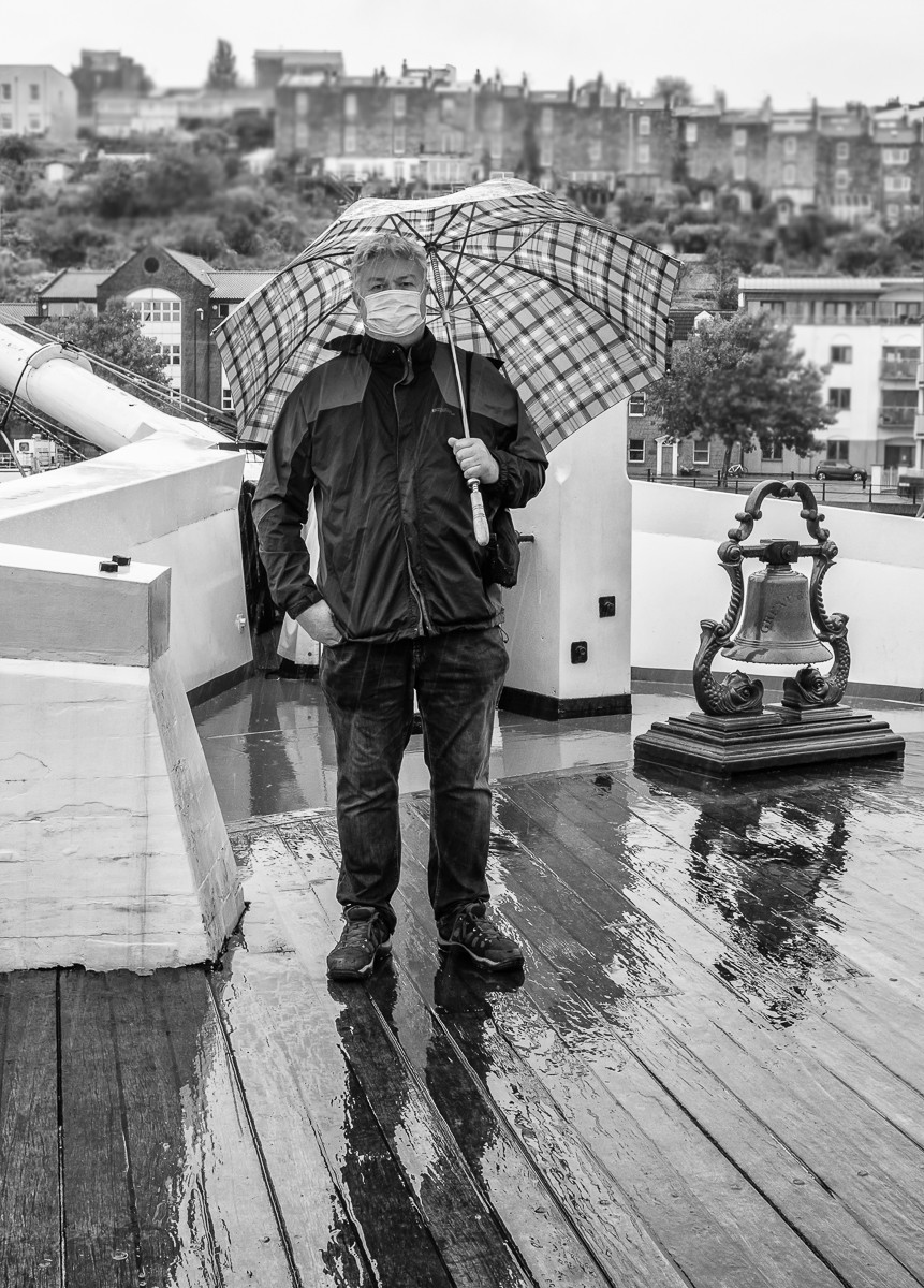 A photograph of a man with a mask on a very wet day.