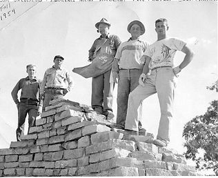 Five men atop the Shrine placing the final stone.